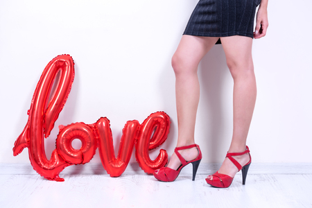 Love word letter shaped red balloon stands near model.Valentines Day concept in studio on a white background.