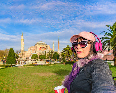 Beautiful woman in hat with takeaway coffee,sunglasses,headphones takes selfie with view of Hagia Sophia on background at sultanahmet park,Istanbul,Turkey
