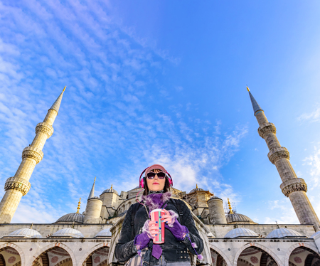 Portrait view of beautiful woman in hat with sunglasses,headphones at Sultanahmet Mosque or Blue Mosque in Istanbul,Turkey  Stock Photo