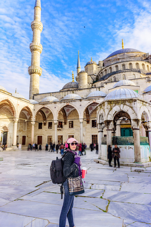 Beautiful woman in hat with takeaway coffee sunglasses,headphones walks at courtyard of Sultanahmet Mosque or Blue Mosque in Istanbul,Turkey