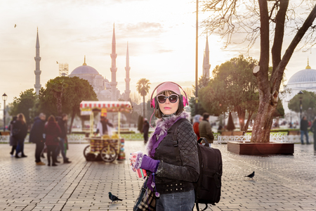 Portrait view of beautiful woman in hat with sunglasses,headphones at Sultanahmet park Mosque or Blue Mosque at background in Istanbul,Turkey