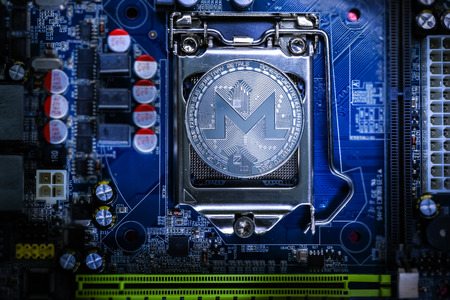 Top view of Monero cryptocurrency physical coin on computer mother board processor.Bitcoin mining farm, working computer equipment concept.
