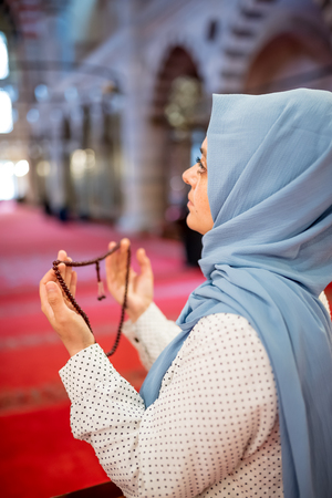 Muslim woman in headscarf and hijab prays with her hands up in air while holding rosary in mosque.Religion praying concept.