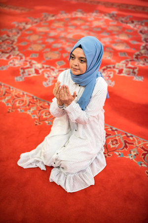 Muslim woman in headscarf and hijab prays with her hands up in air in mosque.Religion praying concept. Archivio Fotografico