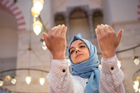 Muslim woman in headscarf and hijab prays with her hands up in air with mosque on background.Religion praying concept. Archivio Fotografico