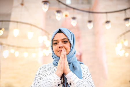 Muslim woman in headscarf and hijab prays while clasping her hands with mosque on background.Religion praying concept.