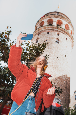 Beautiful attractive happy young trendy girl takes selfie with smart phone and holds fruit juice with view of Galata tower in Beyoglu,Istanbul,Turkey Фото со стока