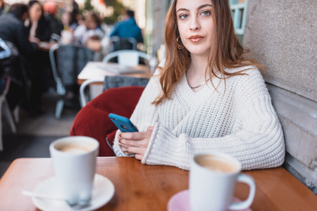 Beautiful attractive young girl in jumper holds and uses smart phone and texting while sitting a cafe.