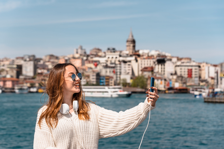 Portrait of beautiful attractive young girl with headphones and smartphone and sunglasses takes selfie with view of Galata Tower in Istanbul,Turkey
