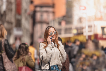 Beautiful attractive young girl in jumper and jeans with headphones and sunglasses uses smart phone while walking in crowd