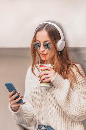 Portrait of beautiful attractive young trendy girl in jumper and jeans with headphones ,sunglasses and smart phone drinks fruit juice while leaning on wall
