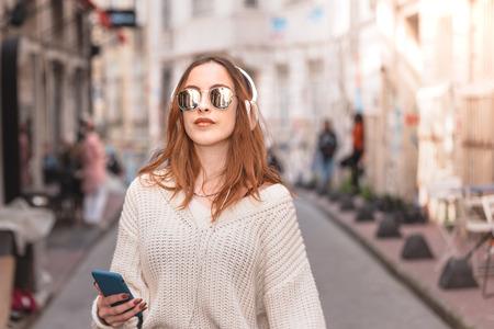 Mooi aantrekkelijk jong trendy meisje in trui en spijkerbroek met koptelefoon, smartphone en zonnebril, luister naar muziek terwijl ze in de menigte loopt Stockfoto