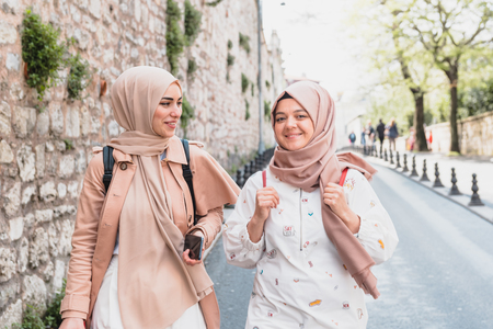 Beautiful Muslim women in headscarf and fashionable modern trendy clothes walk and chat together while having fun.Modern Muslim women lifestyle travel tourist concept