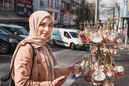 Beautiful Muslim women in headscarf and fashionable modern trendy clothes buys copper Turkish coffee pots.Muslim women lifestyle travel tourist concept