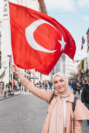 Beautiful Muslim woman in headscarf and fashionable modern trendy clothes hold red Turkish flag at a street. Reklamní fotografie
