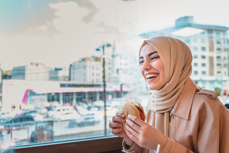Beautiful Muslim woman in headscarf and fashionable modern trendy clothes eats big hamburger in restaurant with happy smiling.Modern Muslim woman lifestyle or business  concept Stock Photo