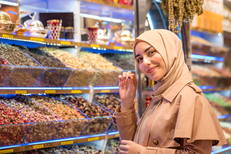 Beautiful Muslim woman in headscarf and fashionable modern clothes looks at spices sold on stall in Egypt Bazaar in Eminonu,Istanbul,Turkey.Modern Muslim women lifestyle travel tourist concept 版權商用圖片