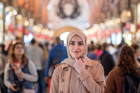 Portrait of beautiful Muslim woman in headscarf and fashionable modern clothes stands among people in grand Bazaar,Istanbul,Turkey.Modern Muslim women lifestyle business or travel tourist concept
