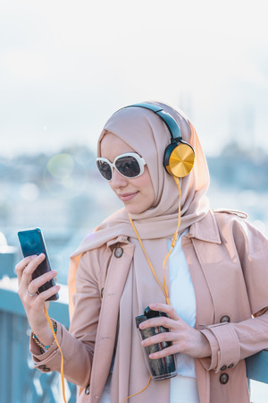 Beautiful Muslim woman in headscarf and fashionable modern trendy clothes with headphones,smartphone and sunglasses takes selfie
