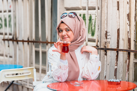 Beautiful Muslim woman in headscarf and fashionable modern clothes drinks Traditional Turkish drinks tea.Modern Muslim women lifestyle or travel tourist concept 版權商用圖片