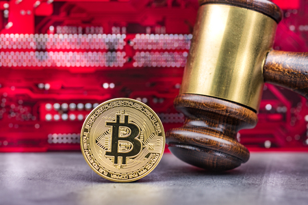 Bitcoin and gavel in front of computer mainboard.Concept image for cryptocurrency