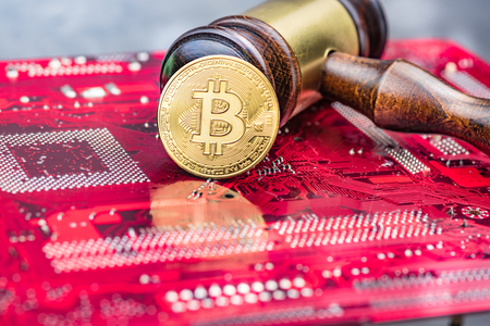 Bitcoin and gavel over computer mainboard.Concept image for cryptocurrency