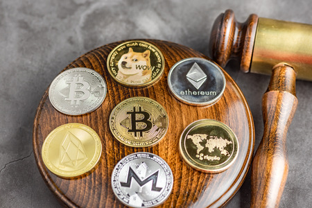 Different cryptocurrencies and gavel over gavel wooden board.Concept image for cryptocurrency Imagens - 122817287