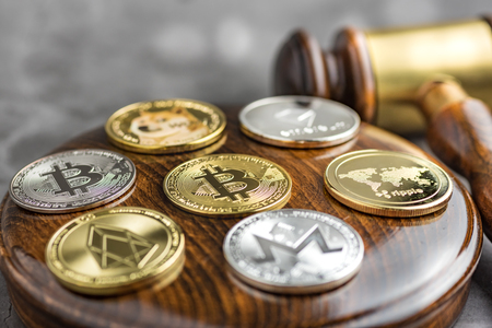 Different cryptocurrencies and gavel over gavel wooden board.Concept image for cryptocurrency Imagens - 122817288