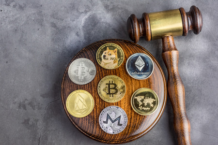Different cryptocurrencies and gavel over gavel wooden board.Concept image for cryptocurrency