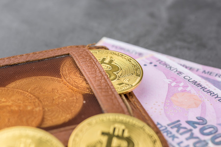 View of metal bitcoins in brown leather wallet and over Turkish Lira banknotes.Concept image for cryptocurrency Imagens - 122817325