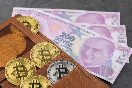 View of metal bitcoins in brown leather wallet and over Turkish Lira banknotes.Concept image for cryptocurrency