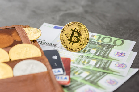View of metal bitcoins and VISA credit cards in brown leather wallet and over Euro banknotes.Concept image for cryptocurrency