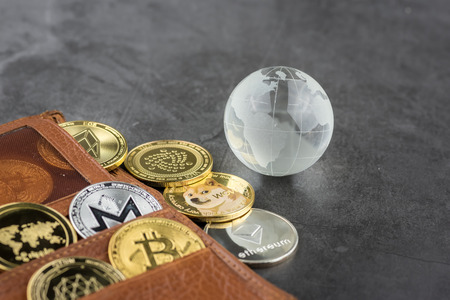 View of different kind of metal bitcoins in brown leather wallet and glass globe .Concept image for cryptocurrency Imagens - 122817417