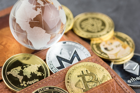 View of different kind of metal bitcoins in brown leather wallet and glass globe .Concept image for cryptocurrency Imagens - 122817418