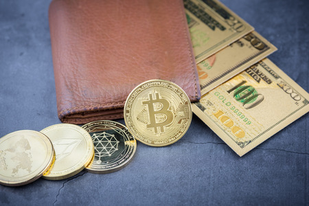 View of metal bitcoins near brown leather wallet and American dollar.Concept image for cryptocurrency