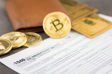 View of metal bitcoins near brown leather wallet and American dollar over tax form.Concept image for cryptocurrency