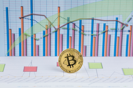 Golden Bitcoin, cryptocurrency physical coin with graph data chart . Virtual cryptocurrency concept.Concept image for cryptocurrency