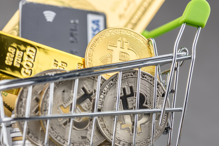 View of metal bitcoins and VISA credit cards and American dollar banknotes in shopping trolley.Concept image for cryptocurrency