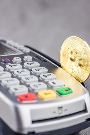 View of metal bitcoin with POS terminal.Concept image for cryptocurrency.Concept of bitcoin payment and cryptocurrency accepted here