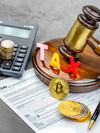 Front view of Bitcoin cryptocurrency in front of gavel with TAX word and calculator.Tax paying concept. Imagens