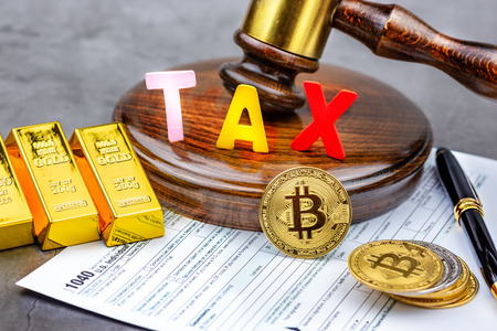 Front view of Bitcoin cryptocurrency in front of gavel with TAX word,calculator and gold bricks .Tax paying concept.