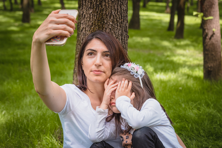 Young mom and little girl takes selfie together.Little girl hides her face.Photo of young mother and her daughter having selfie on green grass Banco de Imagens