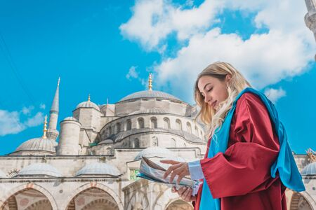 Attractive beautiful girl with covered clothes looks Turkish map with view of Sultan Ahmet Mosque on background in Istanbul,Turkey.Travel Concept