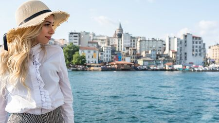 Attractive young beautiful girl stands over Galata Bridge and enjoys view of bosphorus with Galata tower view at background in Istanbul,Turkey.Traveler concept