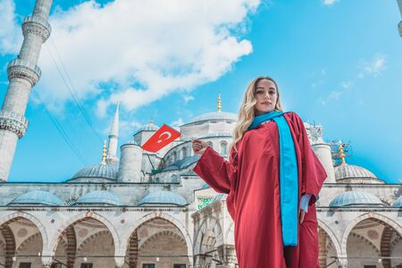 Attractive beautiful girl with covered clothes hold Turkish flag in front of Sultan Ahmet Mosque in Istanbul,Turkey.Travel Concept