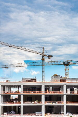 Crane Machines on top of construction building and workers inside with blue clean sky background