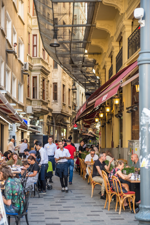 Unidentified people spend time at cafes at a narrow street of popular istiklal street Beyoglu,Istanbul,Turkey .25 July 2019