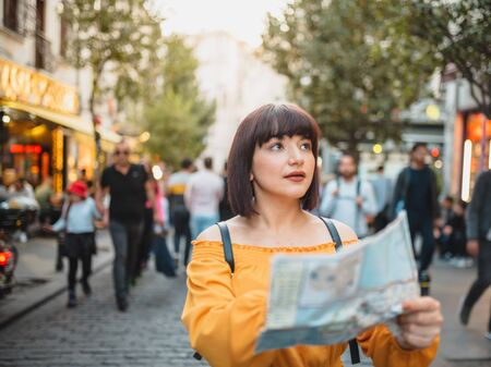 Hermosa joven en ropa de moda con mapa camina por la ciudad y mira a su alrededor.Imagen del concepto de viajero