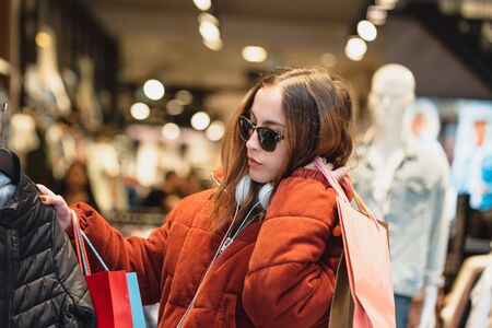 Beautiful attractive young girl in jumper with headphone and sunglasses chooses clothes thinking, looking at clothes while shopping in store