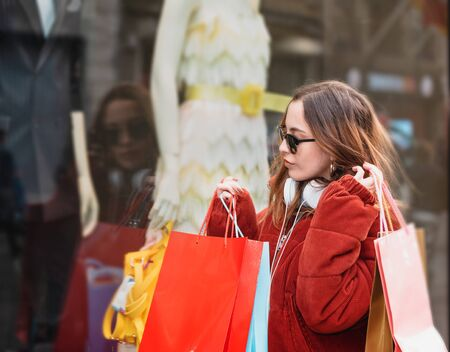 Beautiful attractive young girl in jumper with headphone and sunglasses looks at clothes display windows at shopping store